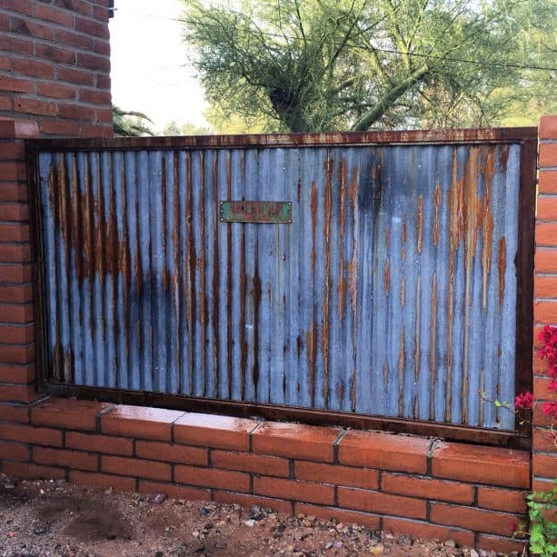 rustic corrugated metal and red brick fence