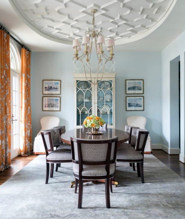 a soothing traditional dining room with soft blue walls and orange floral-patterned curtains