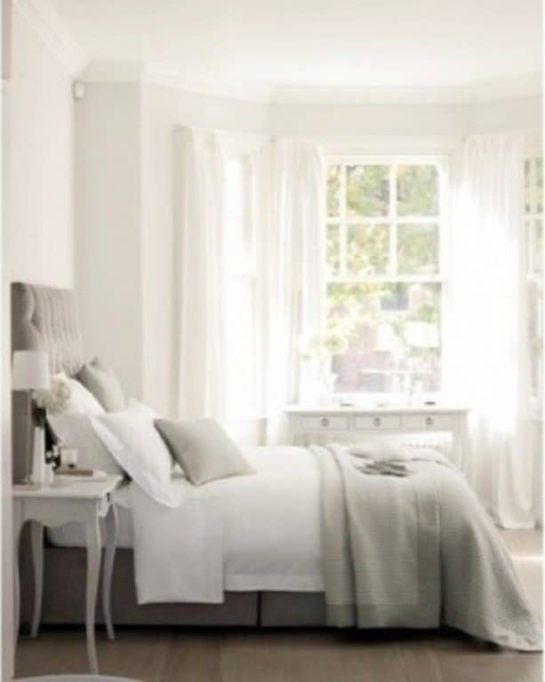 a bedroom with grey bed and white wall