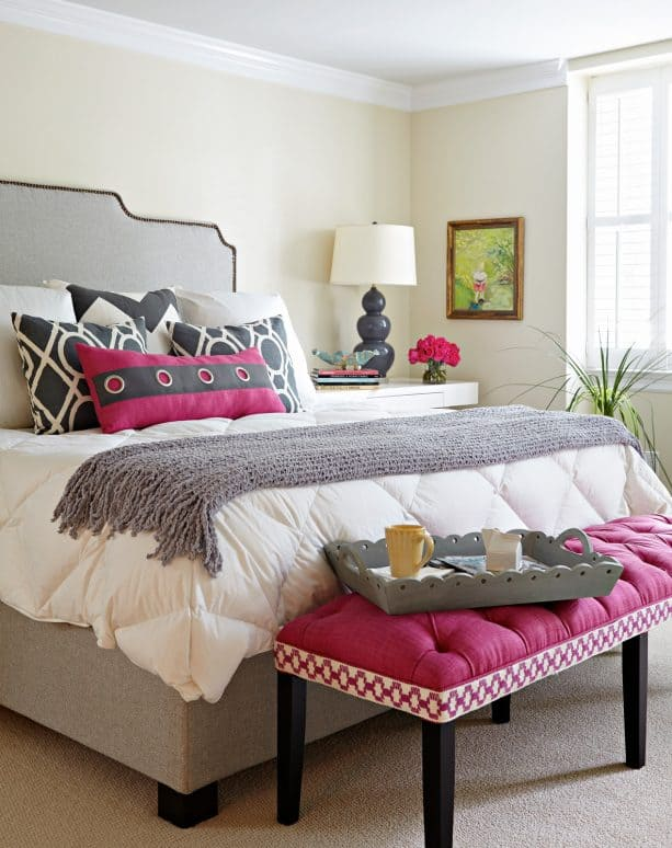 grey bedroom with pink bench