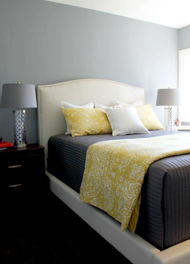 grey and white bedroom with butter yellow blanket and pillows