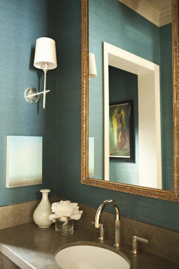a bathroom with golden mirror that go with muted teal grasscloth wall