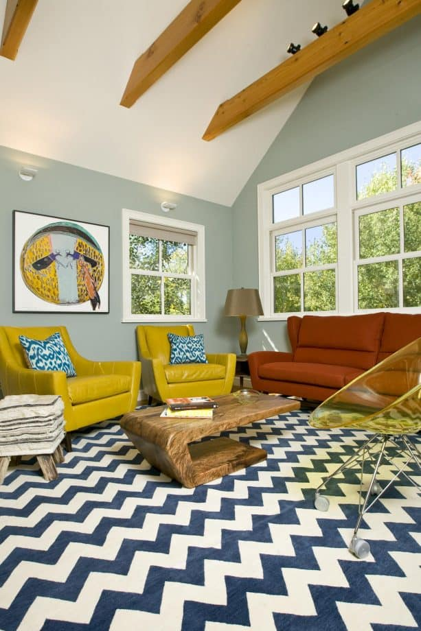 an eclectic living room with grey walls and mustard yellow artwork
