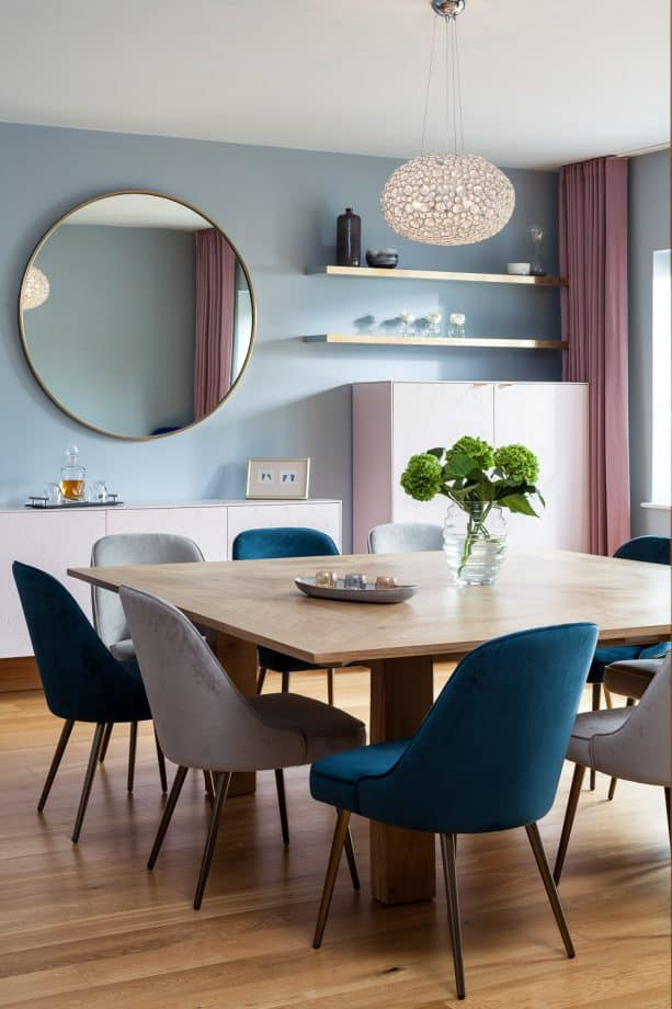 a contemporary dining room with soft blue walls and soft pink full-length curtains)