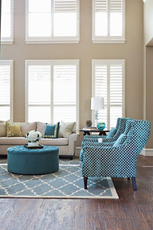 a transitional living room with tan walls and accentuating blue furniture
