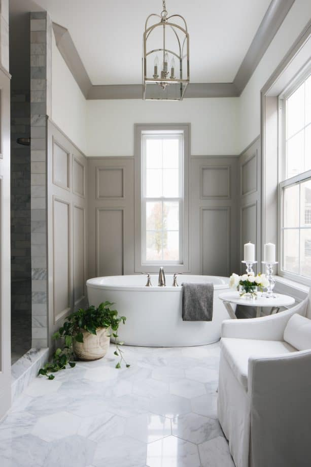 a transitional bathroom with white walls, greige trim, and greige raised-panel wainscoting