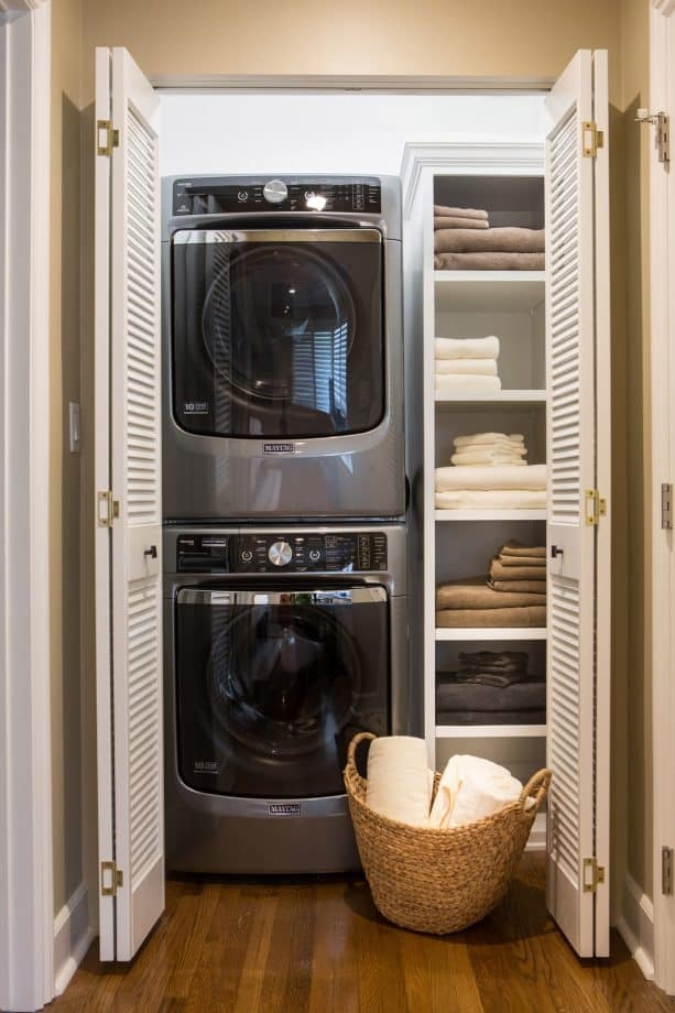 laundry closet with folded louvered doors at the end of a hallway