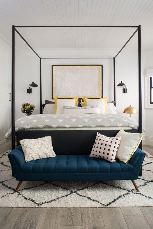 a black canopy bed paired with teal tufted bench at the end