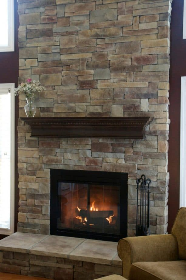 after makeover tall floor to ceiling fireplace with black insert with glass cover and raised hearth with neutral tone tiles