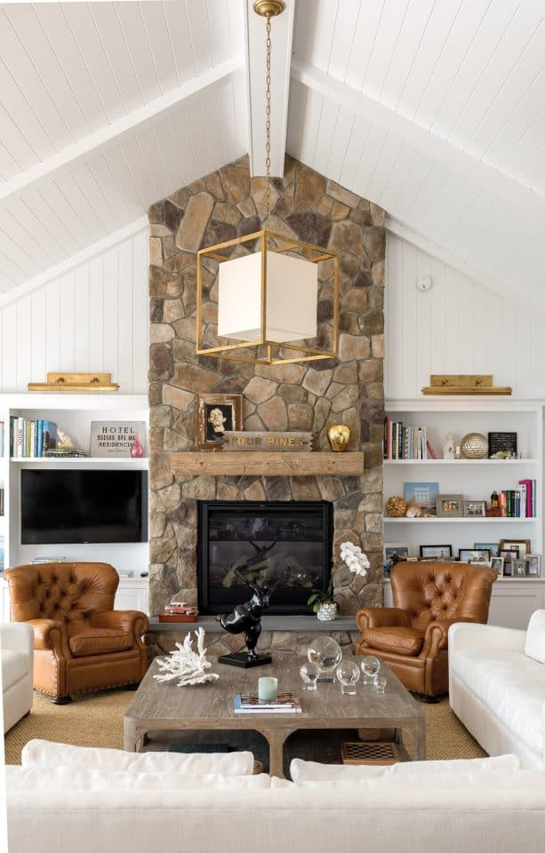 a wall height stone fireplace with white bookshelves that function also for placing a wall-mounted TV