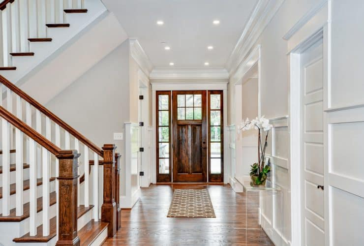a transitional front door with glossy appearance and white trim