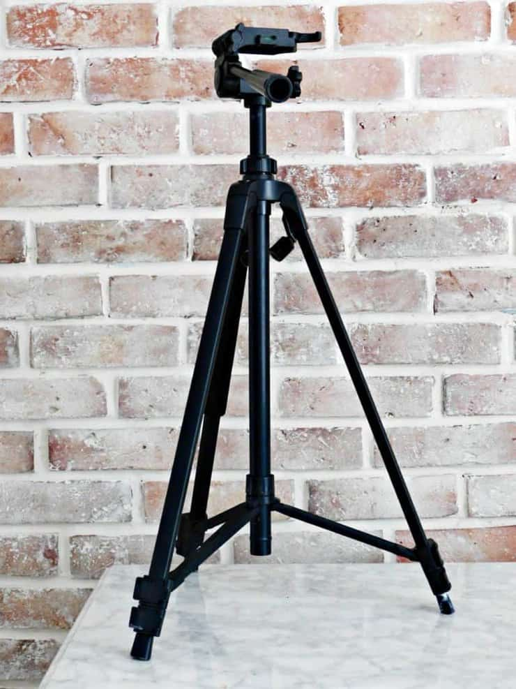 camera tripod in front of brick wall