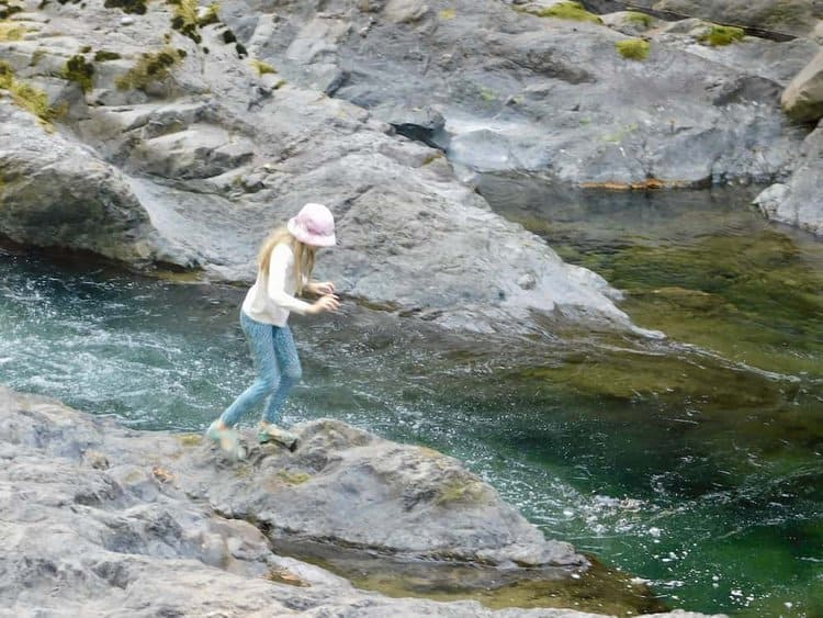 A tween enjoys jumping from rock to rock in the clear, rapid sol doc river.