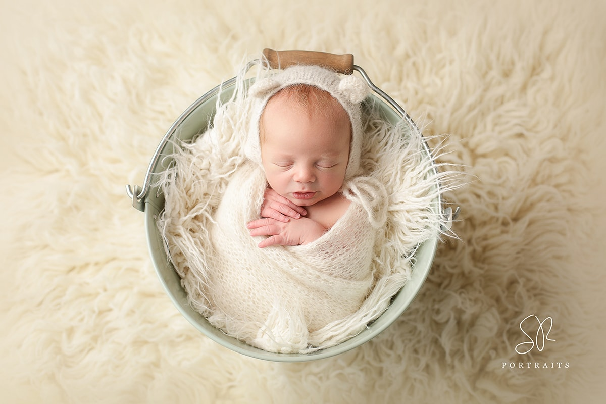 baby wrapped in white in bucket newborn photography leicestershire