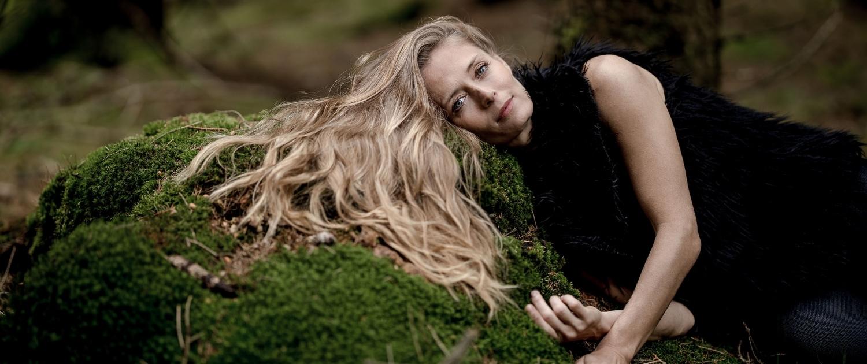 Frau mit langen blonden Haaren liegt seitlich im grünen Moos fotografiert am Bhf Rennsteig im Thüringer Wald mit der Canon EOSR & RF 85mm f/1.2L USM