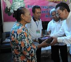 Deputi Seskab Bistok Simbolon menyerahkan sumbangan dalam Bakti Sosial Sambut Natal 2014, di Bintaro, Minggu (14/12)