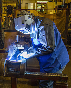 Welder leaning over project in a weld cell