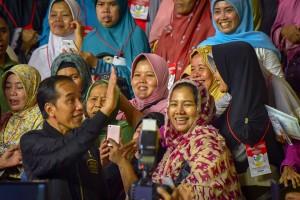 Presiden Jokowi berposes bersama ibu-ibu penerima PKH, di Gelanggang Remaja Jakarta Timur, Jakarta, Senin (3/12) petang. (Foto: AGUNG/Humas)