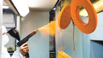 worker usng a powder coating sprayer