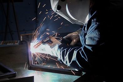 Welder welding a rectangular frame with a MIG gun