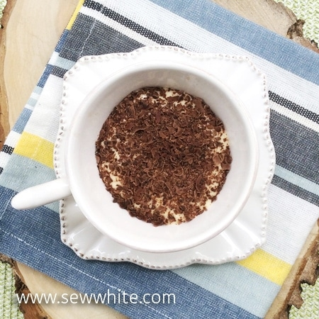 white cup and saucer with Tiramisu with Tea with chocolate shavings on top