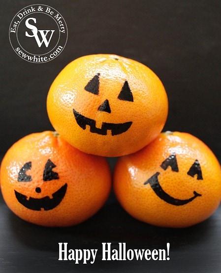 Healthy Halloween Snacks oranges with drawn on pumpkin smiles