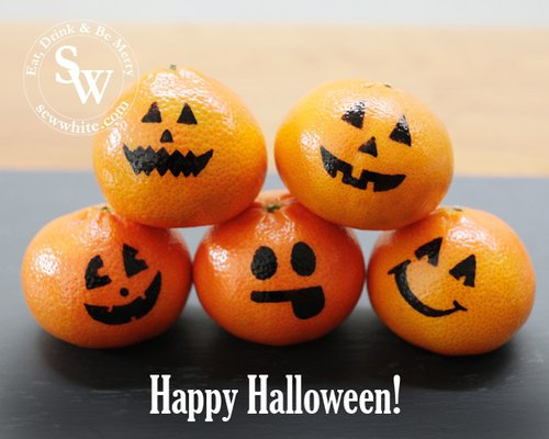 Cute little oranges with pumpkin faces drawn on Healthy Halloween Snacks