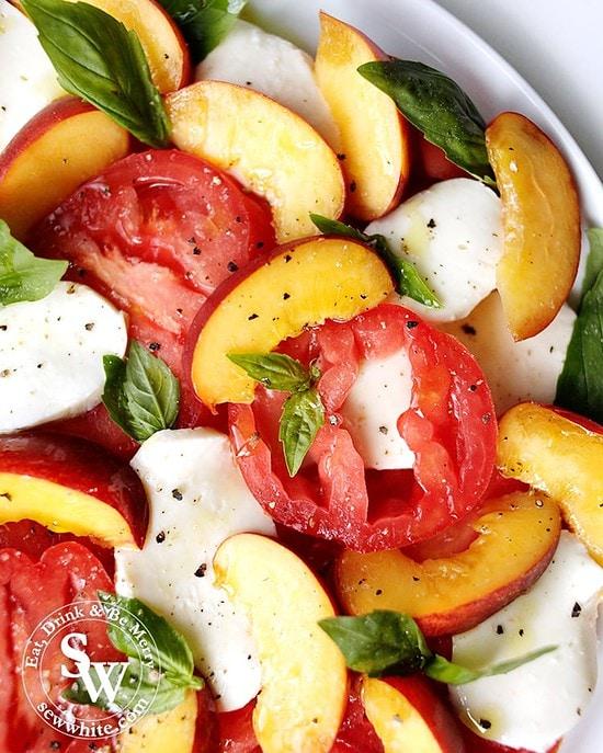 A colour dish of peach slices, mozzarella, tomatoes, basil and black pepper.