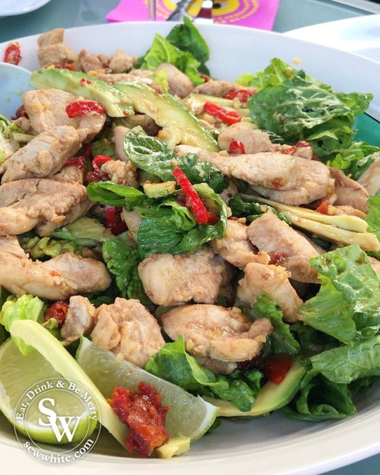 spicy sticky chicken salad iready to serve with fresh red chilli and lime