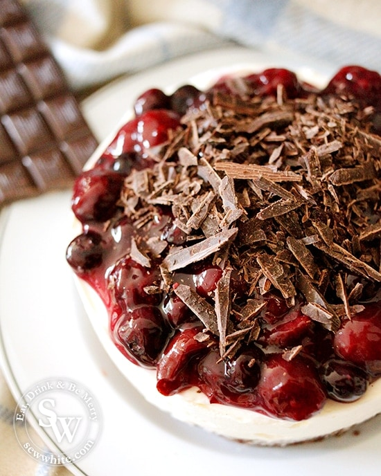 black forest cheesecake close up of the shards of chocolate and cherry compote on the creamy cream cheese base