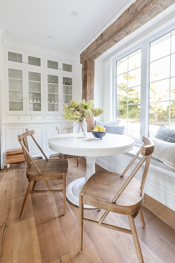 white cabinet glass builtin kitchen cabinets, rustic beams, round white table breakfast nook