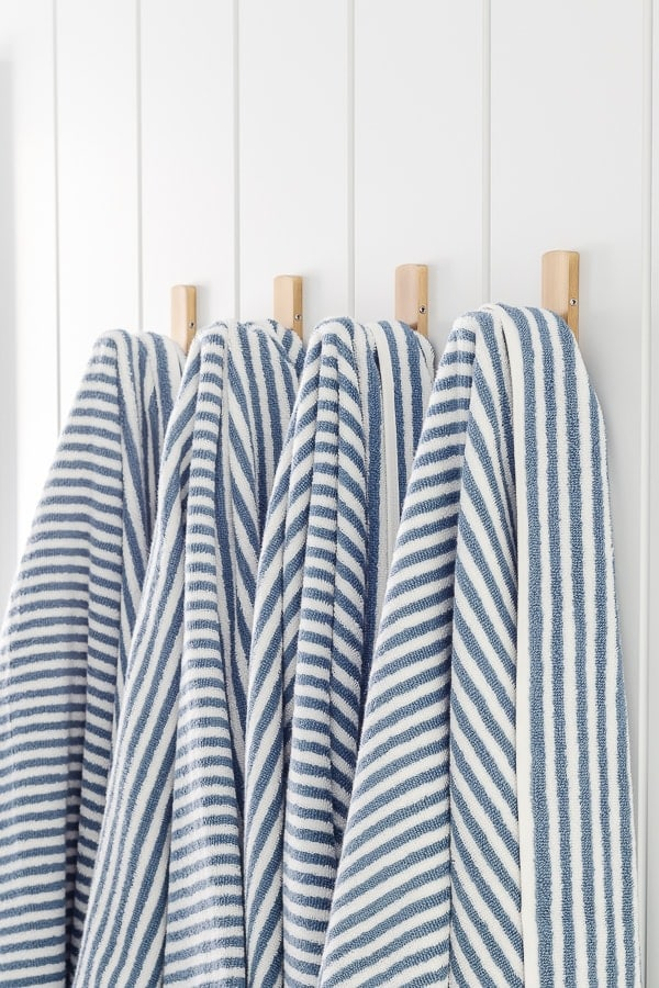blue and white striped towels brass hooks