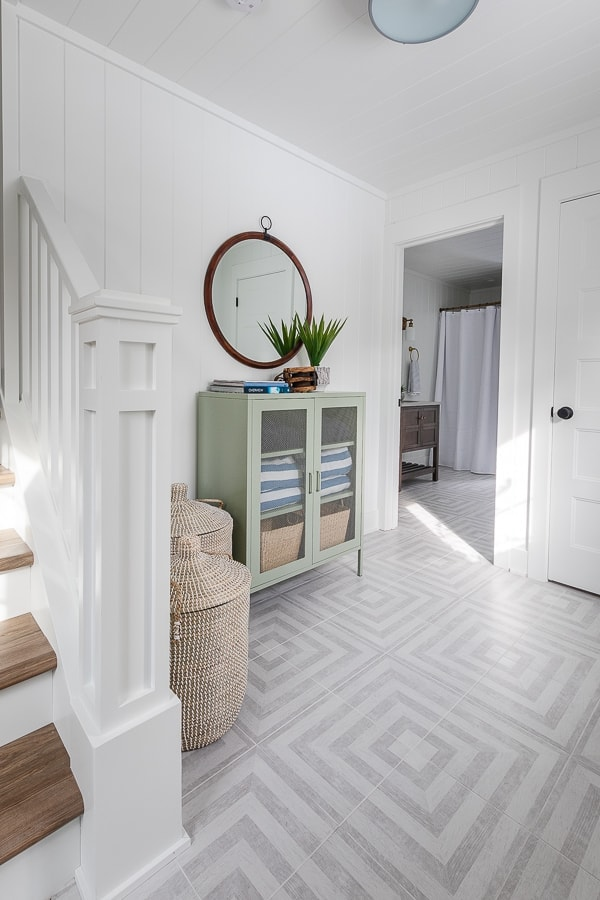 gray and white patterned tile flooring white walls green cabinet