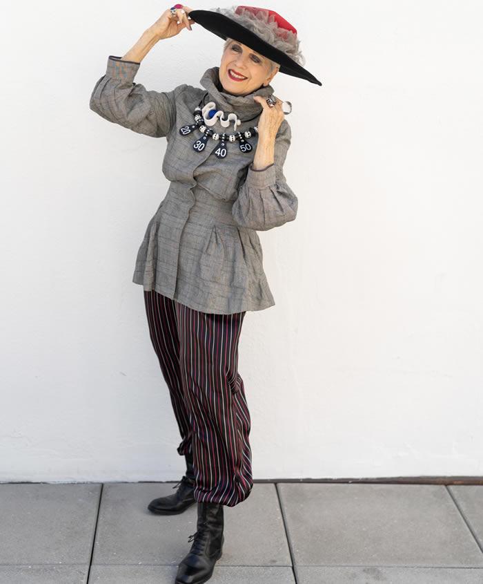 Debra Rapoport wearing a gray jacket with striped pants   40plusstyle.com