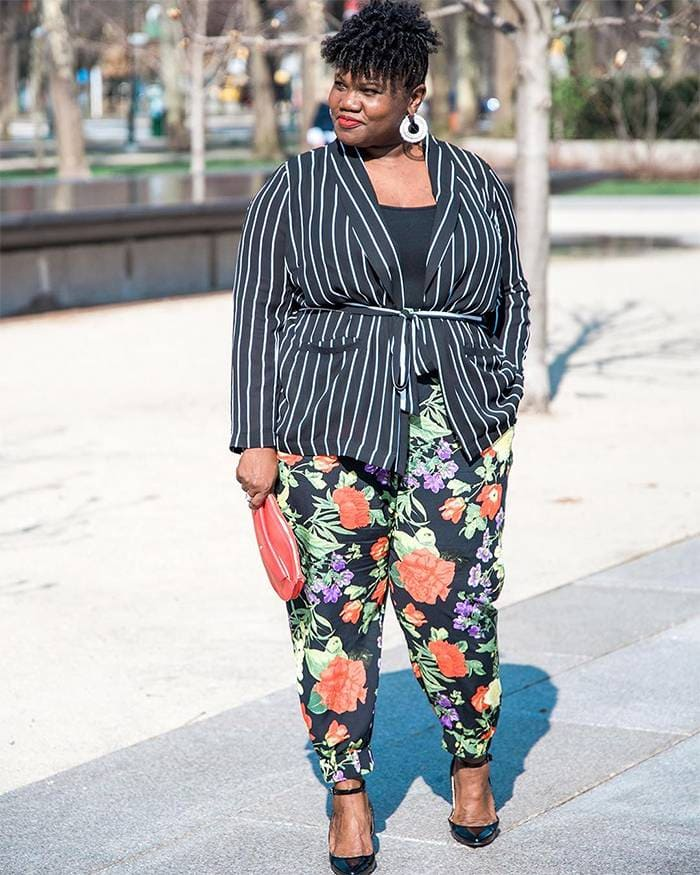 Georgette from Grown and Curvy Women is wearing Black tops over striped belted coat and floral pants with hoop earrings and red clutch | fashion over 40 | 40plusstyle
