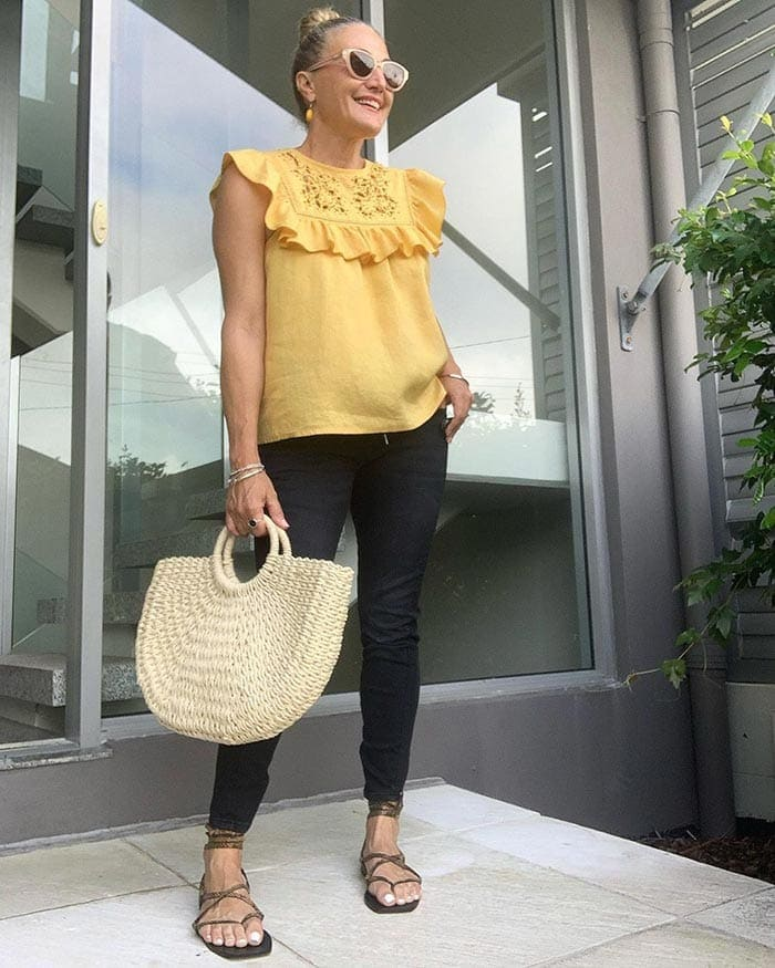 Melinda in a yellow top and dark jeans | 40plusstyle.com