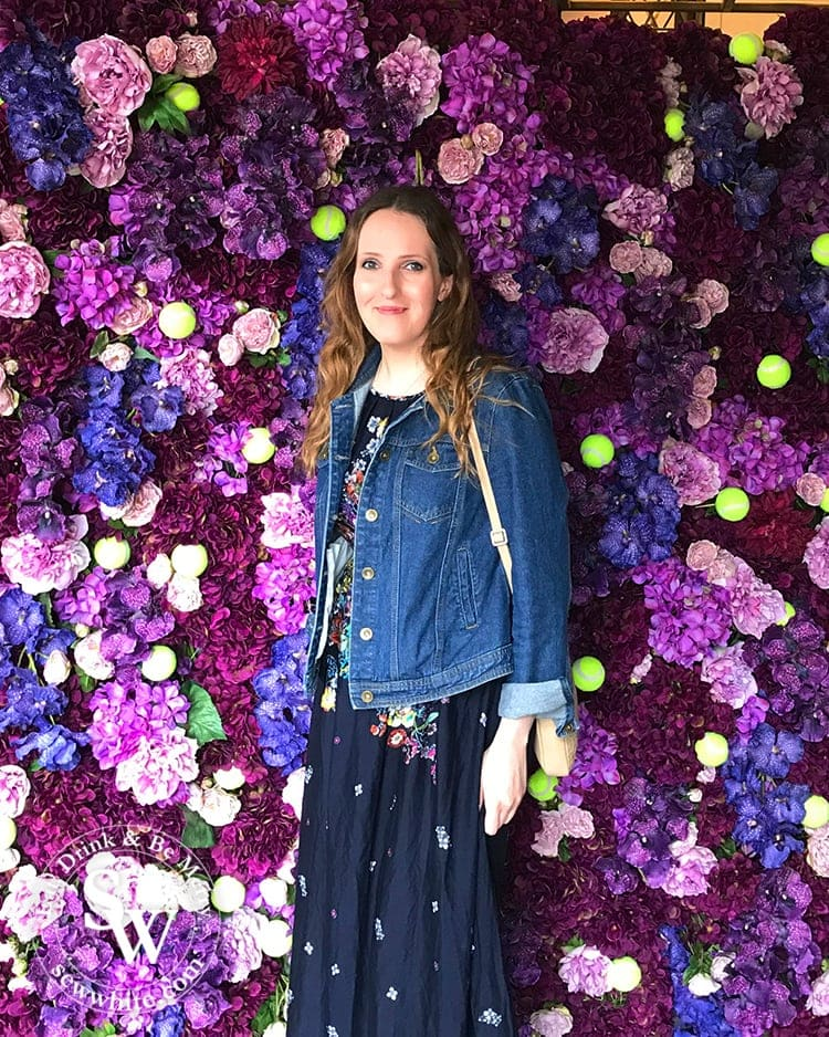 Sisley White at the dog and fox in wimbledon village at their Wimbledon inspired purple and pink flower wall studded with tennis balls.