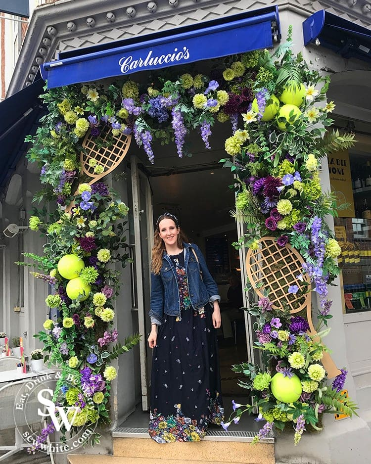 Sisley White at Carluccio's in Wimbledon Village who have a beautiful flower arch filled with over size tennis balls and rackets. In the Wimbledon purple and green colours.