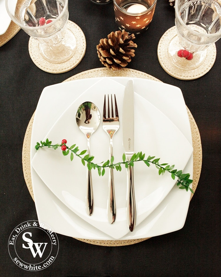 White plates tied with Christmas garland on the Black Gold and Red Christmas Table