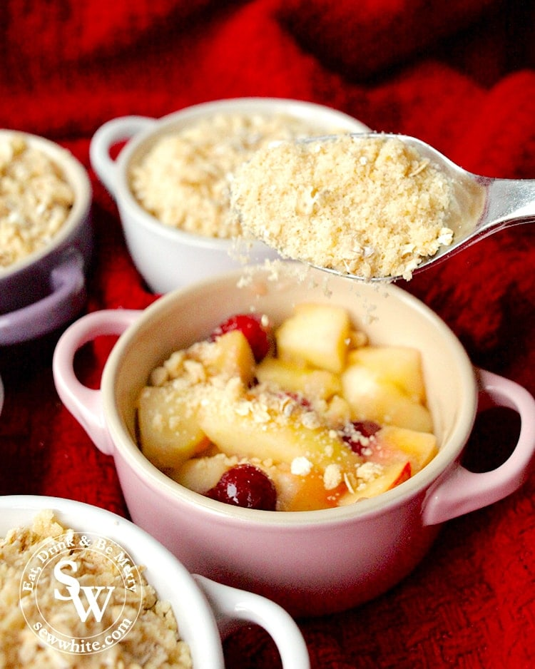 Adding the crumble to the softened apple and cranberries. apple and cranberry crumble recipe