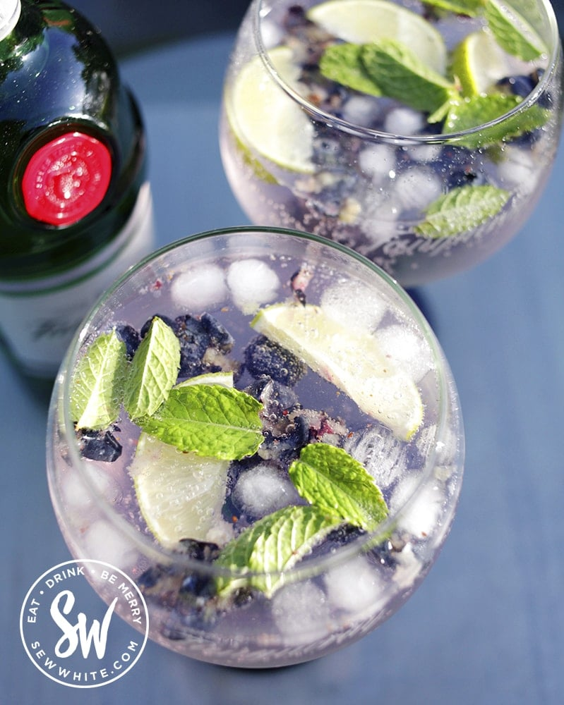 purple gin and tonic ade with fresh berries in a green stemed gin and tonic glass. Blueberry Gin and Tonic Recipe