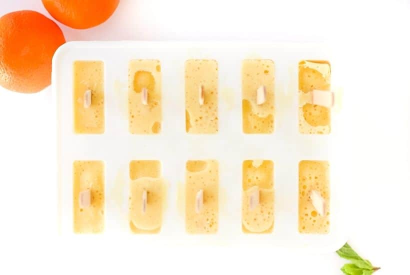 Orange Julius Popsicles are creamy, smooth, and full of orange flavor. If you love an orange creamsicle, you are going to love this variation of the classic frozen treat. This Copycat Orange Julius Pops Recipe is perfect for a hot summer day. Try this homemade orange creamsicle recipe today.