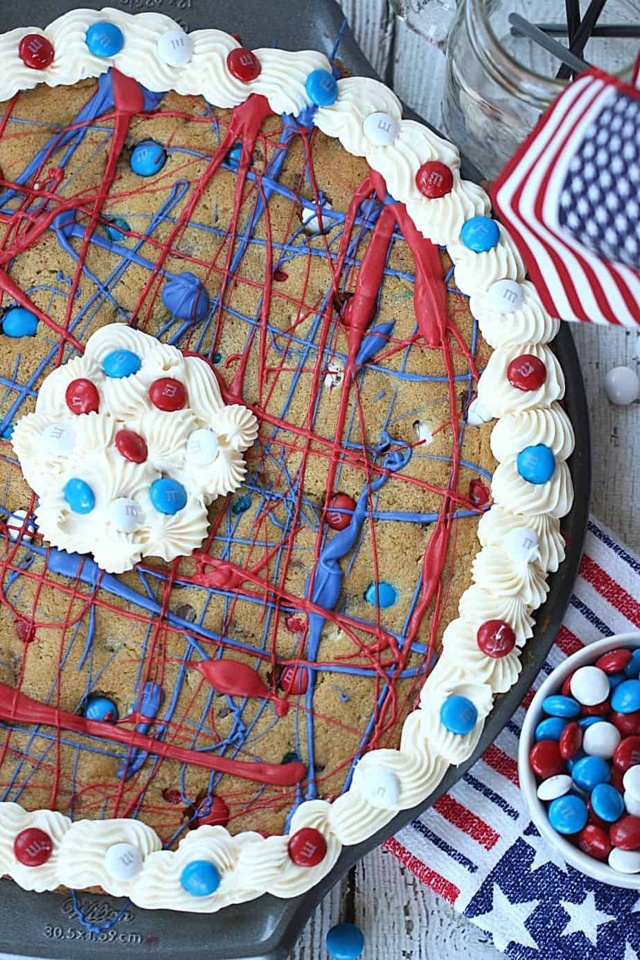 This festive Firecracker Cookie Cake recipe is the perfect dessert for your patriotic celebration! This easy chocolate chip cookie is decorated in red, white and blue and is a perfect recipe for the 4th of July, Memorial Day or Labor Day.