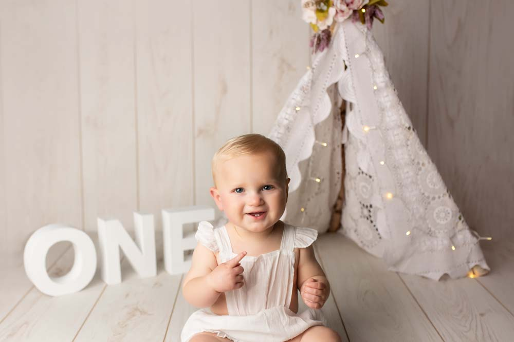 First birthday girl holding out her fore finger sitting in front of a teepee
