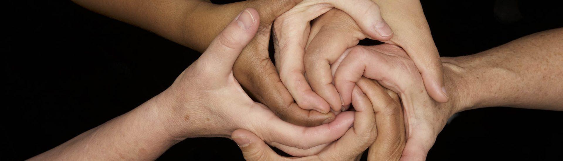 7 Hände verschiedenener Personen, die diese zusammenführen