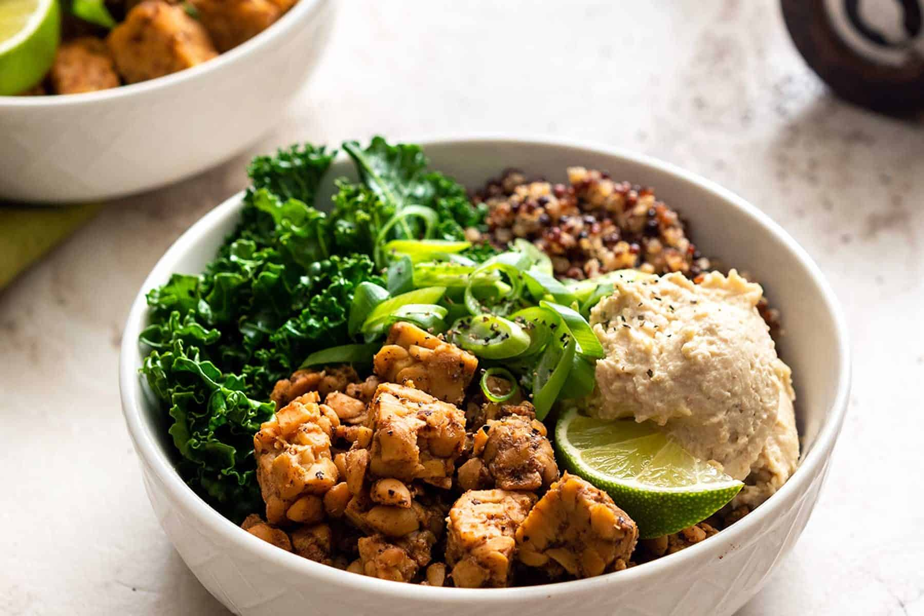 Two white bowls with kale, tempeh, quinoa, and bean dip on a marble background