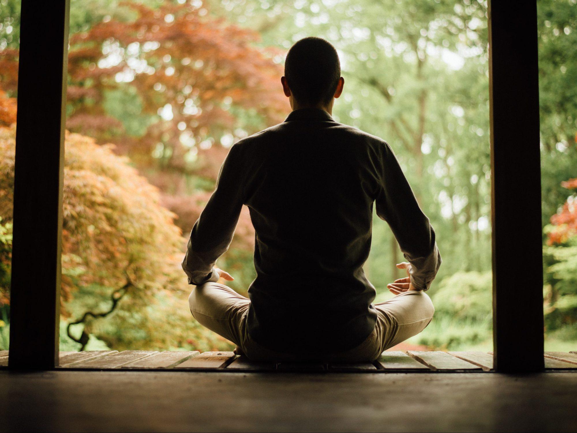 Trainer die in meditatiehouding zit: Hoe werkt mindfulnesstraining precies?