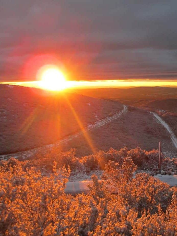 AFbeelding van opkomende zon met een weg door de bergen: Individueel coachingstraject, vindt je eigen weg.