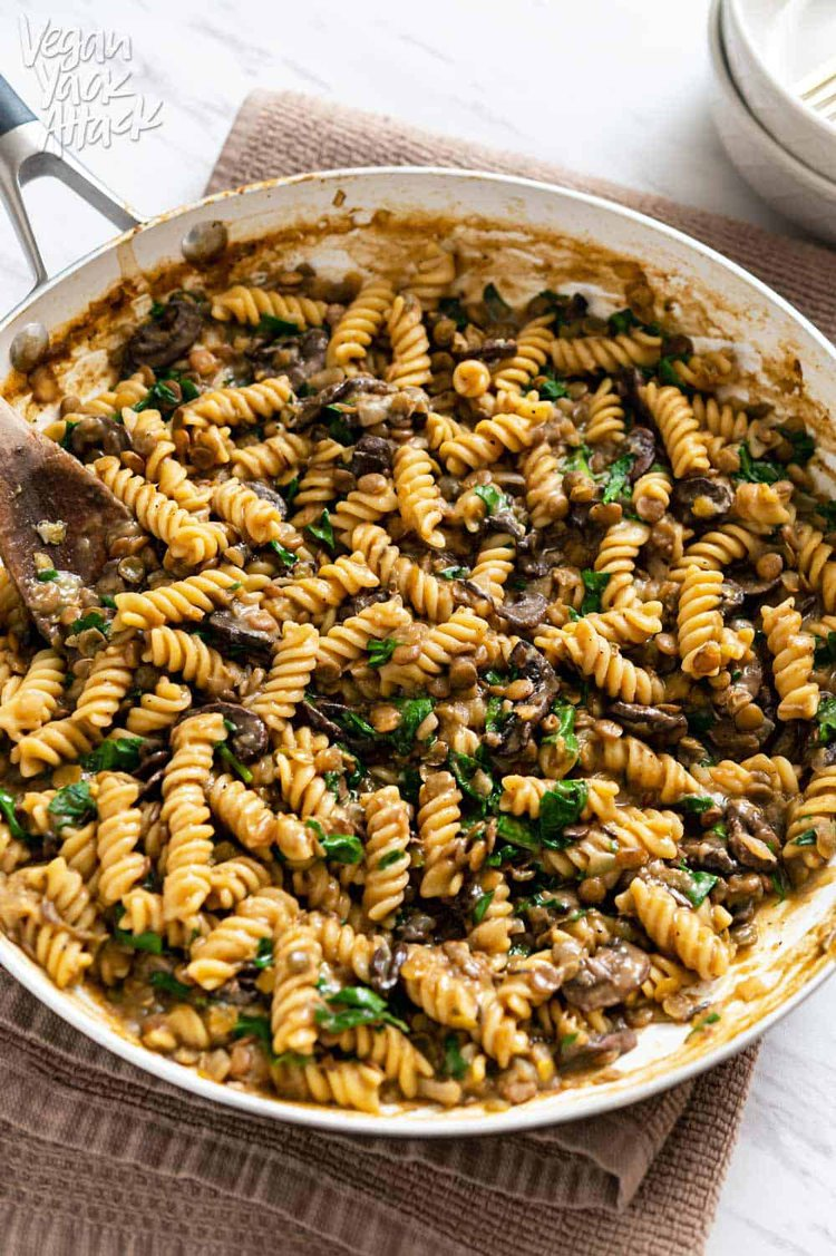 Image of a close-up of one-pot lentil mushroom pasta in a large pan sitting on a towel