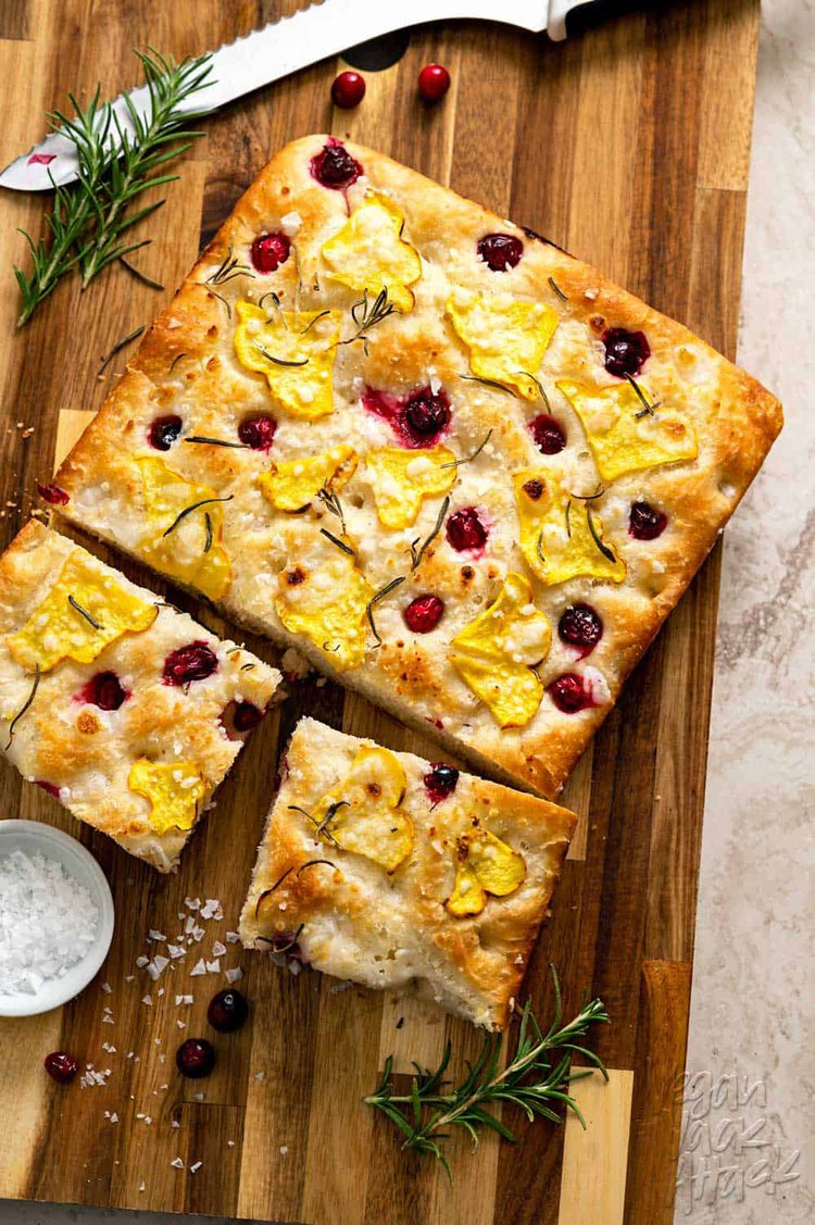 Focaccia topped with squash and cranberries on a wood cutting board